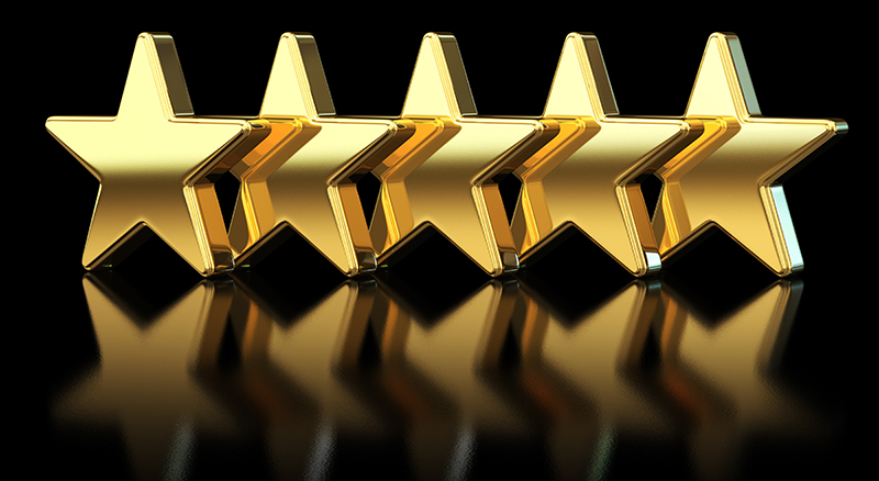 Five gold stars lined up not facing forward slightly askew with a black reflective background