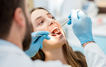 Banner Bank benefits illustrated by a dentist examining brunette woman's teeth with mirror