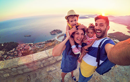 Family of four mom dad toddler son and daughter taking a selfie standing on a rock patio looking down on the ocean coastline