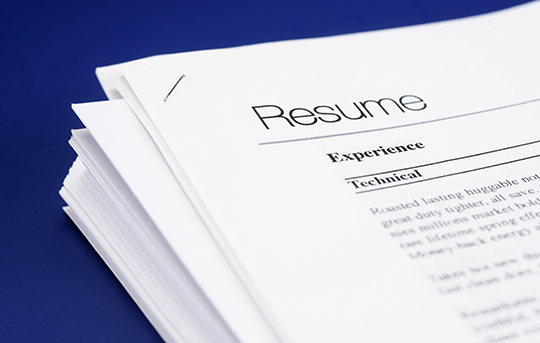 Stack of resumes piled up on a table with blue background