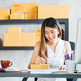Female business-owner addressing packages to be sent