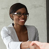 Female business-woman closing a deal with a handshake
