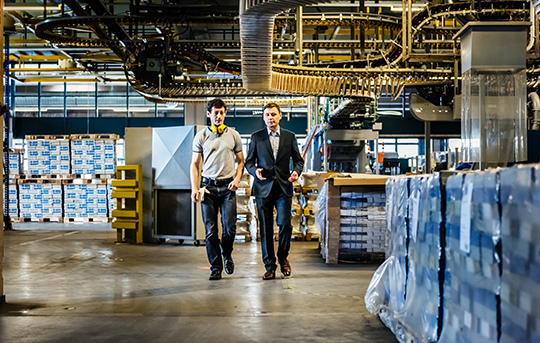 Two men walking and discussing in warehouse