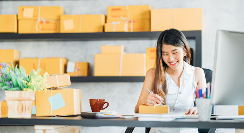 Businesswoman addressing packages to be sent out