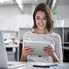 Woman smiling at desk using tablet