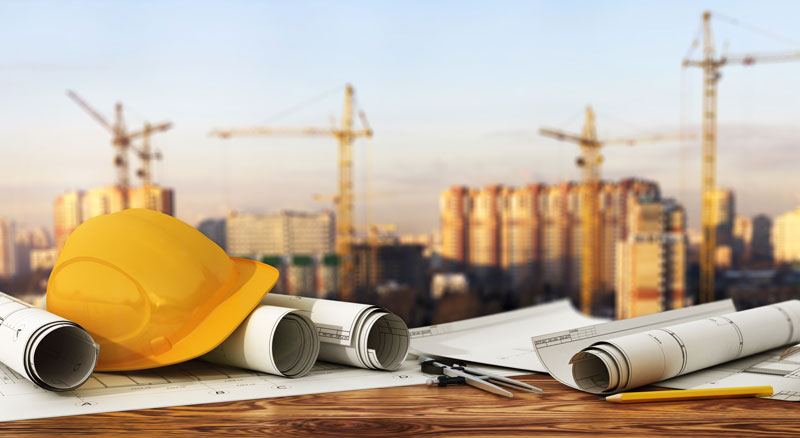 Hard hat and design plans on an income property construction site financed by Banner Bank