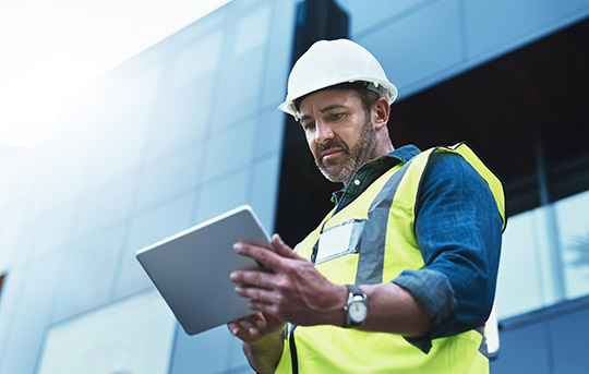 Building contractor or owner on tablet
