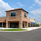 Stucco strip mall with blue and green awnings