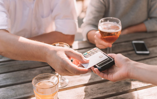 Patron pays for drinks with contactless card reader
