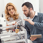 Dark haired man and blonde haired woman working on a 3D printer