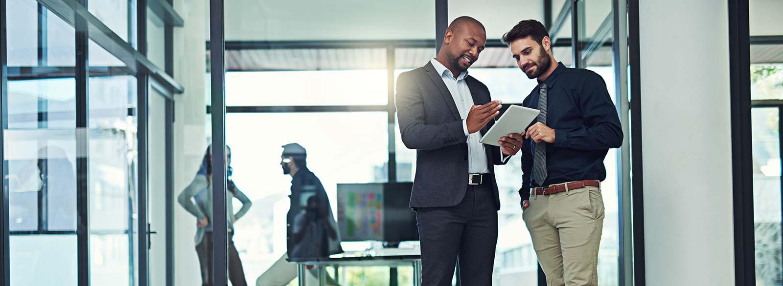 Two business men talking in an office hallway
