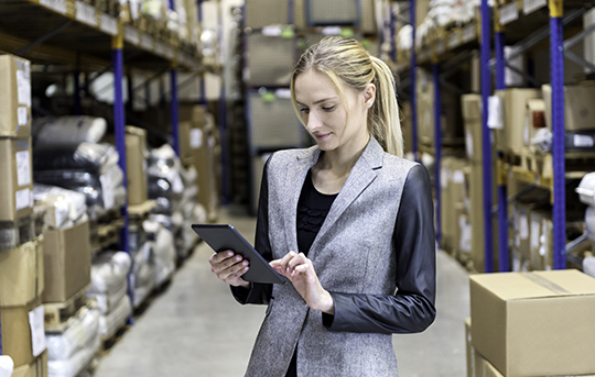 Blonde woman in a warehouse with a tablet checking inventory