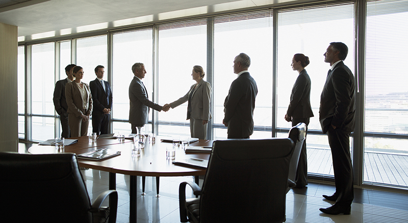 Group meeting in a large conference room two people in the center shaking hands as if two groups are making a deal
