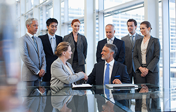 Group of business people in two groups each group has four people three standing and one person seated in each group the people seated are shaking hands