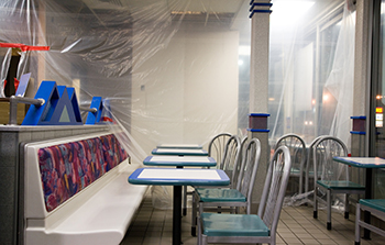 Shot of a restaurant being refurbished with a clear plastic tarp hung in the background a long bench seat on  one side of table and chairs on the other