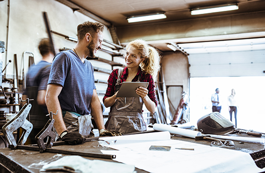 White man with brown hair and beard speaking with a blonde haired white woman standing at a work table inside a big manufacturing shop
