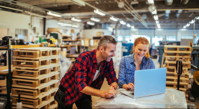 Man and woman in warehouse look at laptop screen together