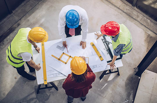 Aerial view of four people in hard hats reviewing construction plans