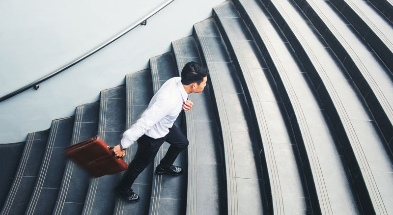 Asian man, mid-step, in business attire walking up cement steps carrying a brown leather briefcase