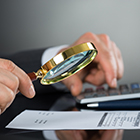 Caucasian male hands holding a magnifying glass examining a statement and the other hand is on a calculator