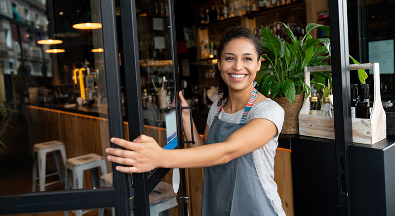 Business owner opening doors for business