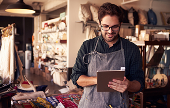 Caucasian male shop owner with brown hair, short beard and glasses wearing an apron holding a tablet