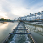 Photo of a water treatment plant at sunset with trough running through middle of body of water