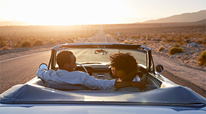 Couple driving car in desert