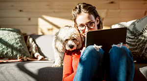 20 or 30 something person looking at tablet next to dog