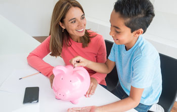 Mom watching son put coins in a piggy bank
