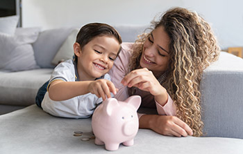 Mother and child putting coins in piggy bank