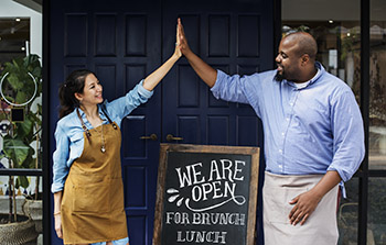 Business owners high fiving with we are open for brunch lunch sign