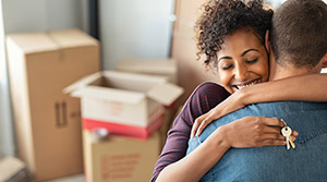 Couple hugging with house keys and packing boxes