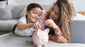 Child putting coins into piggy bank with parent assist