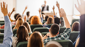 Students raising hands in college lecture hall