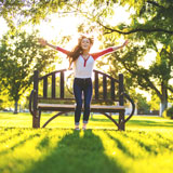Young woman in park jumps for joy