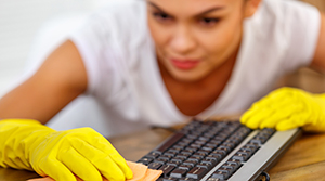 Woman with dark hair wearing yellow rubber cleaning gloves using a rag to clean a computer keyboard