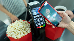 Person paying for popcorn with digital wallet on iphone