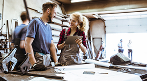 Brown hair bearded man speaking with blonde woman in a welding shop