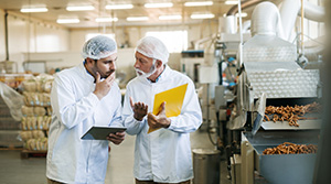 Two managers of a food production plant talking in the plant