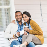 Couple enjoys coffee on porch swing