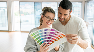 Man and woman in an empty white room looking at color swatches