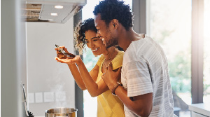 Couple tasting sauce in new kitchen