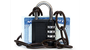 Social Security card covered by a black padlock and black chains