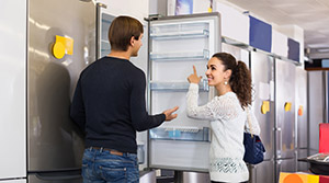 Couple looking at fridge in appliance store