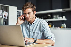 Man on phone looking at accounts on laptop