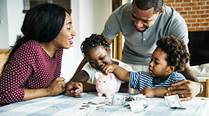 African American mom and dad with son and daughter at a table with cash and coins surrounding a pink piggy bank