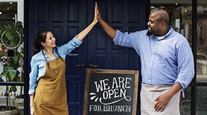 Shop owners giving high fives in front of we are open sign
