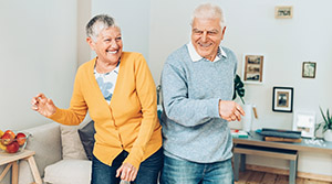 Older couple dancing in living room