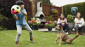 Child throwing ball to dog in back yard
